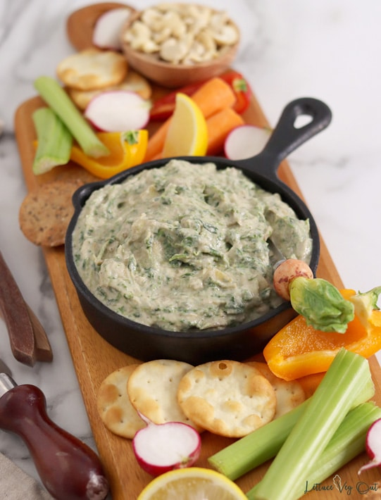 Spinach artichoke dip in a cast iron pan with a radish-shaped butter knife in the dip. Pan sits on a board loaded with crackers and vegetables.