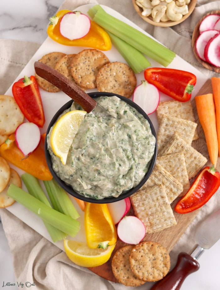 Top view of a small black bowl of spinach artichoke dip, garnished with a lemon wedge and with a wood-handled butter knife in it. Bowl in on a square board topped with crackers and vegetables. The board sits on a crumpled light brown towel.