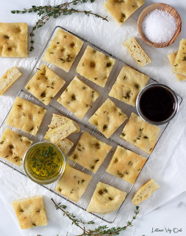 Top view of a wire rack covered with square pieces of focaccia bread, a small jar of olive oil and small jar of balsamic vinegar. Around the board is decorated with more bread, thyme and a wooden dish of salt.