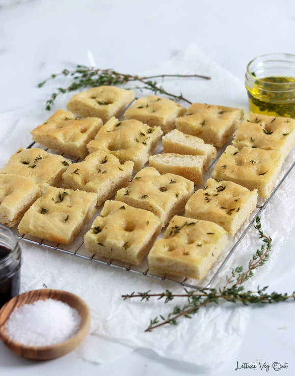 Wire rack topped with herbed focaccia bread with thyme, olive oil, balsamic vinegar and a wood dish of salt decorating around the board.