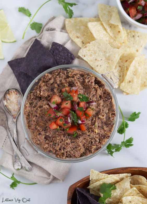 Top view of a glass dish of black bean dip topped with a scoop of fresh tomato salsa and surrounded by blue and white corn tortilla chips, two metal serving spoons, cilantro and lime slices.