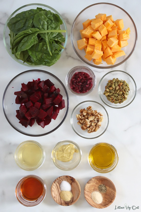Top view of an arrangement of ingredients in glass and wood dishes. From top moving left then down: spinach; cubed pumpkin; cubed beetroot; pomegranate seeds; pumpkin seeds; walnuts; apple cider vinegar; Dijon mustard; olive oil; maple syrup; onion powder + garlic powder; salt + pepper.