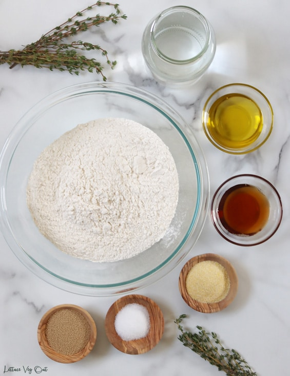 Top view of an arrangement of ingredients in glass or wood bowls. Large bowl of flour in the center with other ingredients around the right edge. From top: water; olive oil; maple syrup; cornmeal; salt; yeast. Decorated with fresh thyme.