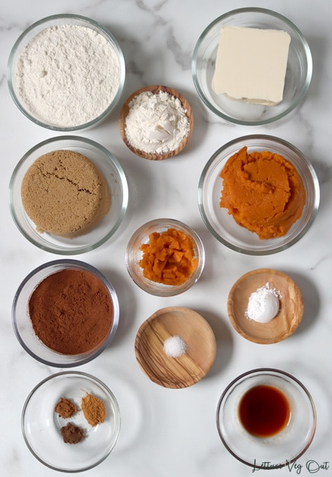 Top view of an arrangement of ingredients in glass or wood dishes. From top left working right then down: flour; butter; more flour; brown sugar; pumpkin puree; more pumpkin puree; cocoa powder; salt; baking powder; cinnamon + nutmeg + allspice; vanilla extract.