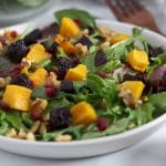 Square cropped image of a close up of a plate of salad topped with cubes of roasted pumpkin and roasted beetroot, pumpkin seeds, walnuts, pomegranate seeds and dressing.