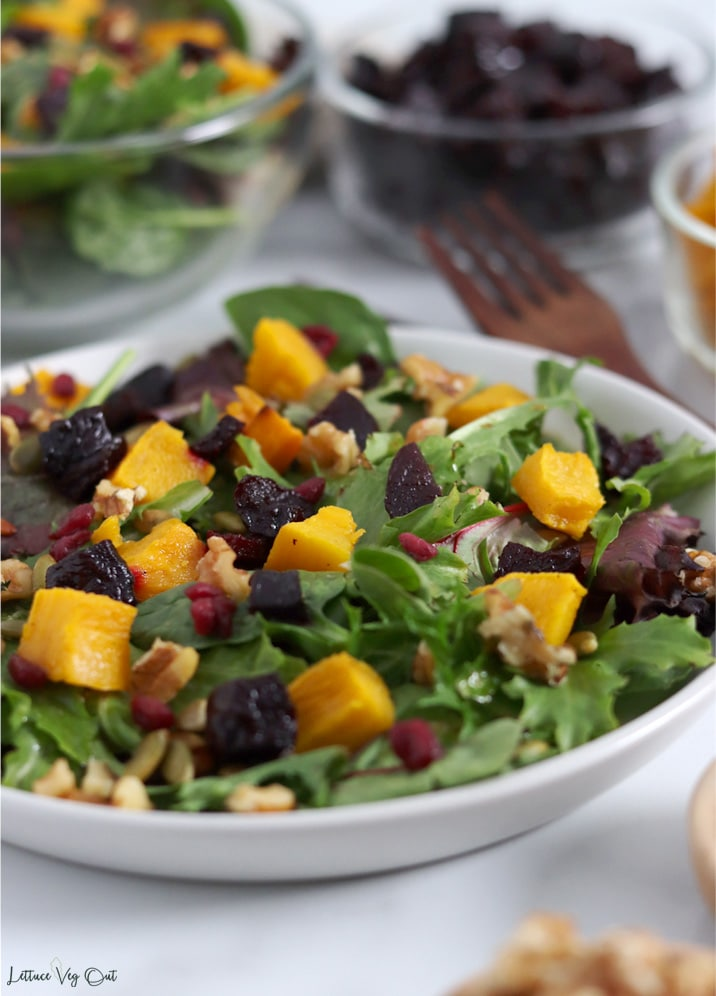 Close up of a plate of salad topped with cubes of roasted pumpkin and roasted beetroot, pumpkin seeds, walnuts, pomegranate seeds and dressing. In the background are glass bowls with extra salad, roast pumpkin and beetroot.