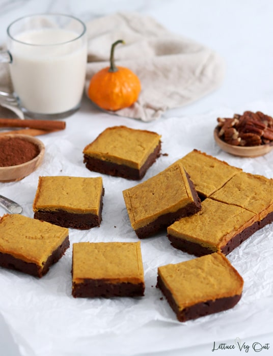 Arrangement of nine pumpkin and chocolate brownies on parchment paper with decorations behind the brownies (glass of milk, dish of cocoa powder, cinnamon sticks, small pumpkin and crumpled beige towel).