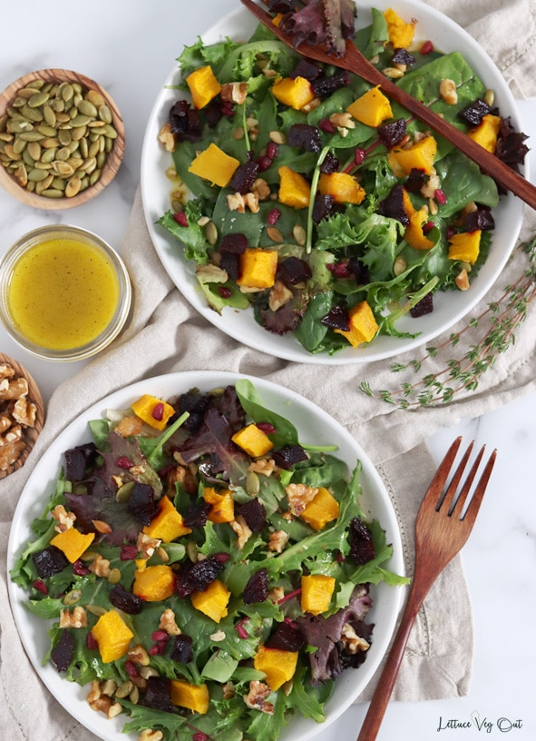 Top view of two plates of salad topped with roasted pumpkin and beetroot, walnuts, pumpkin seeds and pomegranate seeds. Plates sit on a light brown towel. Wood forks, fresh thyme, jar of salad dressing and dish of pumpkin seeds decorates around the plates.