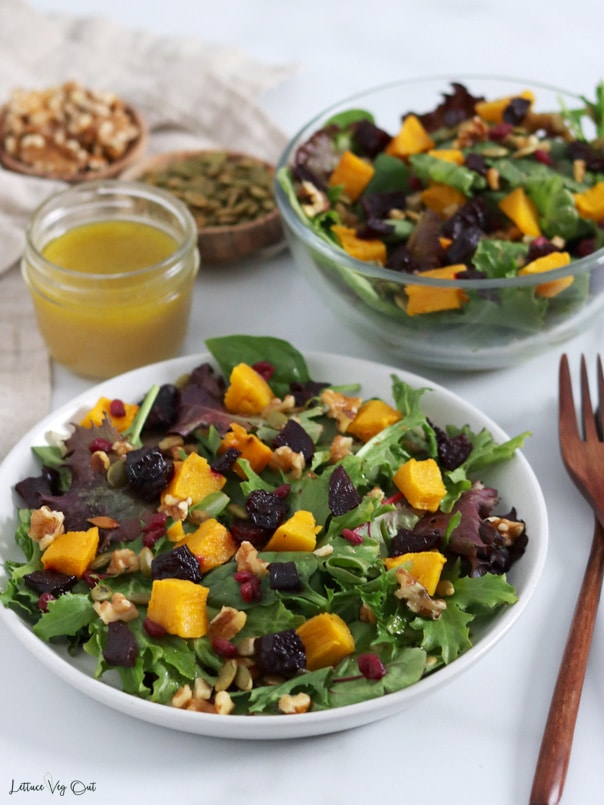 Plate of salad topped with roast pumpkin and beetroot cubes along with pomegranate seeds, walnuts and pumpkin seeds. A glass bowl of salad sits behind the plate along with a glass jar of dressing and blurred wood dishes filled with pumpkin seeds and walnuts.