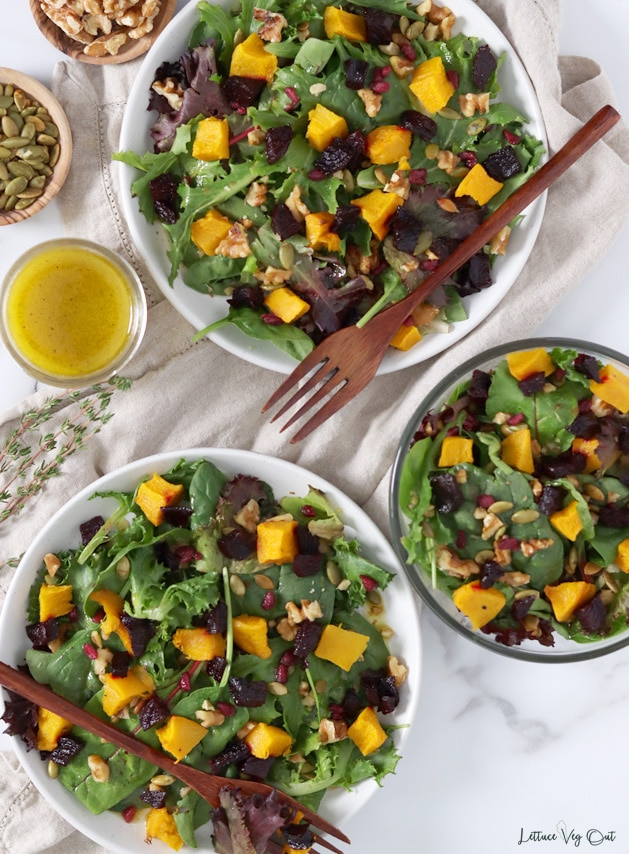 Top view of two plates and a glass bowl all filled with roasted pumpkin and beetroot salad. Image decorated with wood forks, a light brown towel under the plates, fresh thyme, a jar of salad dressing and dishes of walnuts and pumpkin seeds.