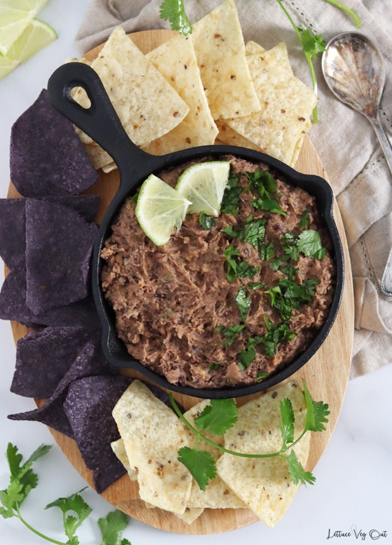 Top view of a small cast iron pan filled with black bean dip that is garnished with a sprinkle of cilantro and two lime pieces. Pan sits on a wood board that is covered with blue and white corn tortilla chips and sprigs of cilantro.