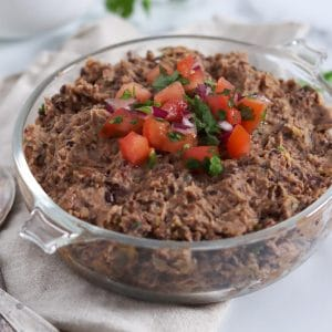 Square cropped close up of a glass dish filled with black bean dip that is garnished with fresh tomato salsa.