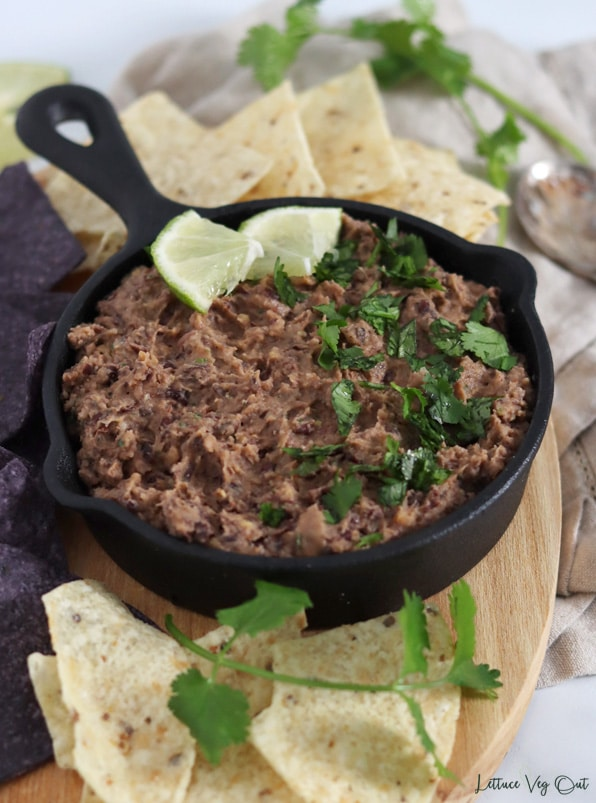 Close up of a cast iron pan filled with black bean dip that is garnished with chopped cilantro and lime pieces. Pan surrounded by white and blue corn chips with sprigs of cilantro.