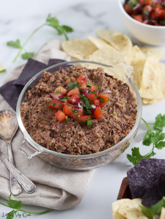Glass bowl of black bean dip topped with a scoop of fresh tomato salsa sitting on a folded beige bowl and surrounded with blue and white corn chips behind the bowl. Bottom right corner shows the corner of a wood bowl of chips and top right corner shows a bit of a white bowl filled with salsa.