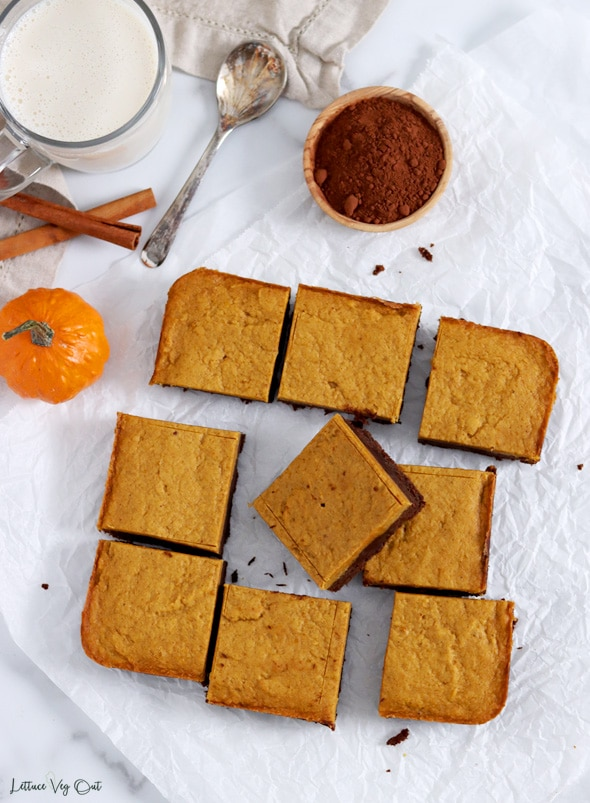 Top view of an arrangement of nine square pumpkin brownies with the center brownie resting up on the one to its right. Top left corner of image decorated with cinnamon sticks, a small pumpkin, a spoon, a dish of cocoa powder and a glass of milk.