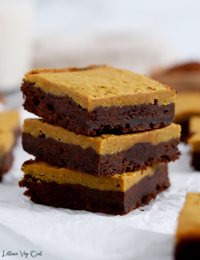Close up of a stack of three chocolate pumpkin brownies (chocolate layer on bottom, orange pumpkin layer on top). Other blurred brownies surround the stack.