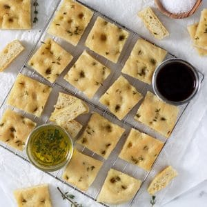 Square cropped image of the top view of a wire rack covered with square pieces of focaccia bread, a small jar of olive oil and small jar of balsamic vinegar.