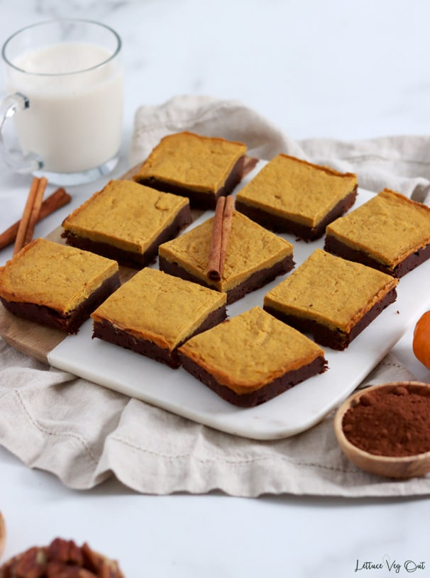 Nine chocolate pumpkin fudge brownies on a half marble, half wood board that sits on a beige towel and is decorated around with cinnamon sticks, cocoa powder and a glass of milk.