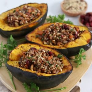 Square cropped image of three roasted acorn squash halves that are stuffed with wild rice, cranberry and walnut filling sitting on an oval wood board that is garnished with parsley.